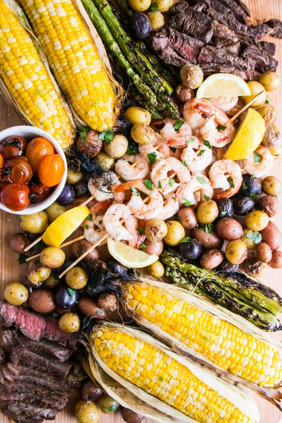 A surf-n-turf bbq board with lots of vegetables and all cooked on the grill!