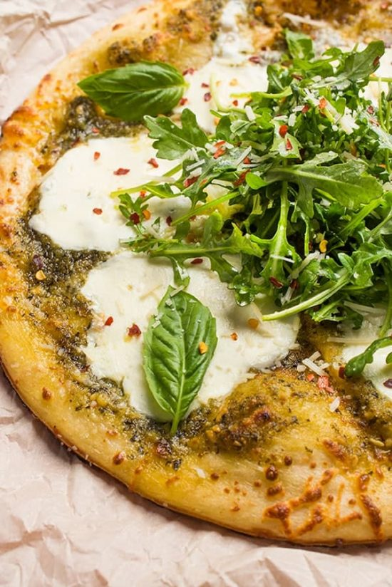 This fast and easy grilled pizza recipe is made with bright pesto, fresh mozzarella and topped with a lemony arugula salad.