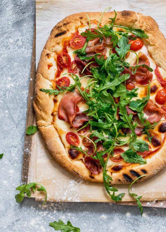 Grilled Prosciutto Arugula Pizza Recipe- A delicious and irresistible smokey pizza with a 4 cheese blend, salty prosciutto and crispy arugula.